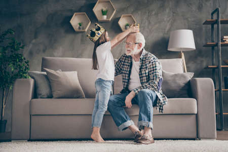 Profile photo of funny aged old grandpa golden crown head little pretty granddaughter playing famous people roles stay home quarantine safety modern interior living room indoors