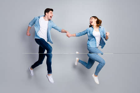 Full length photo of funny lady handsome guy crazy two people jumping high up running shopping center sale season wear casual denim shirts outfit isolated grey color background