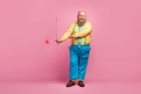 Full length body size view of his he nice funky dreamy glad bearded guy shooting amorous arrows aim goal meeting arrangement isolated over pink pastel color background