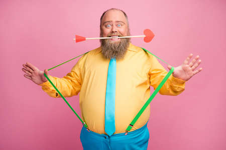 Portrait of his he nice friendly funky glad positive bearded guy holding in teeth mouth amorous arrow pulling suspenders having fun isolated over pink pastel color background Banque d'images