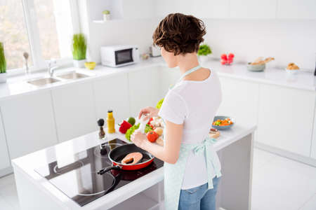 Rear behind view photo of beautiful housewife lady put add salt fresh raw salmon fillet steak on flying pan dieting cooking hobby dinner wear apron stand modern kitchen indoors