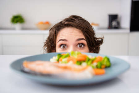Close up photo of housewife lady cunning tricky hungry eyes look from under table ready to eat grilled salmon trout fillet steak garnish portion modern kitchen indoors