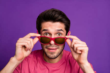 Closeup photo of attractive guy taking off sun specs watch see crazy cool offer low shopping prices season opening wear casual pink t-shirt isolated purple color background