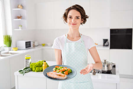 Have your gastronomy masterpiece, Photo of housewife lady chef showing grilled salmon trout fillet steak roasted garnish cook dinner one person portion wear apron modern kitchen indoors Archivio Fotografico
