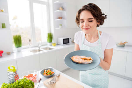 Photo of housewife lady chef hold ready grilled salmon trout fillet steak need garnish cook dinner one person portion eyes closed enjoy smell wear apron modern kitchen indoors