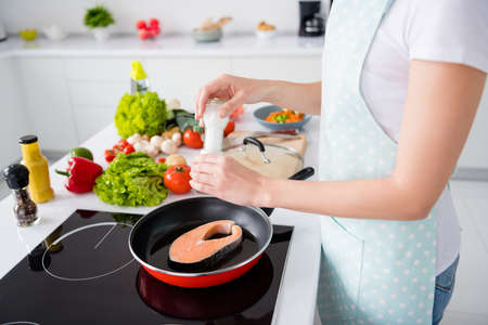 Cropped photo of housewife lady hands put fresh raw salmon fillet steak lying, flying pan adding spices salty cooking family dinner wear apron t-shirt stand modern kitchen indoors Archivio Fotografico