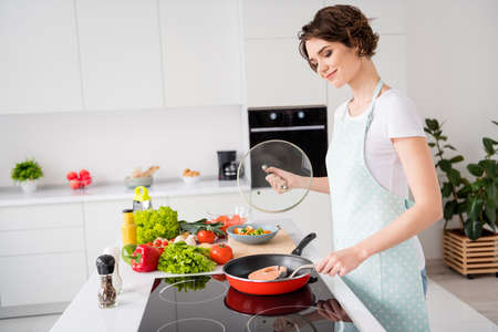 Profile photo of beautiful cheerful housewife lady put fresh raw salmon fillet steak on flying pan turning side dieting cooking hobby dinner wear apron stand modern kitchen indoors