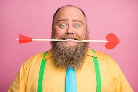 Close-up portrait of his he nice funky glad positive bearded guy holding in teeth mouth shooting amorous arrow 14 February congrats isolated over pink pastel color background Banque d'images