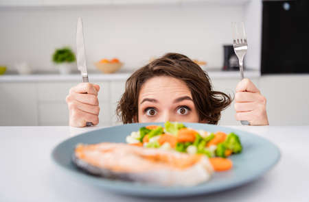 Close up photo of housewife lady cunning tricky hungry eyes look from under table ready to eat grilled salmon trout fillet steak garnish portion hold fork knife modern kitchen indoors