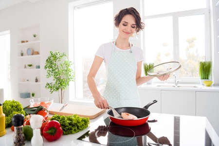 Photo of beautiful cheerful housewife lady put fresh raw salmon fillet steak on flying pan keeping diet cooking hobby family dinner wear apron stand modern kitchen indoors