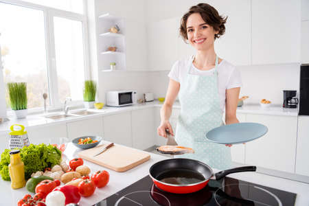 Photo of pretty housewife lady put grilled salmon trout fillet steak flying pan on plate ready roasted condition cook family dinner wear apron t-shirt stand modern kitchen indoors