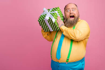 Portrait of his he nice funky curious bearded positive glad guy holding in hands dotted giftbox greeting from colleagues guessing whats inside isolated over pink pastel color background