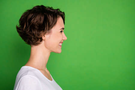 Closeup profile photo of attractive cheerful lady good mood beaming smile wavy bobbed hairdo look empty space wear casual white t-shirt isolated bright green color background Imagens