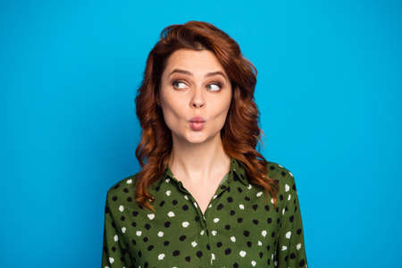 Closeup photo of pretty curly lady look interested side empty space shy sending air kisses handsome guy wear green dotted office shirt isolated bright blue color background