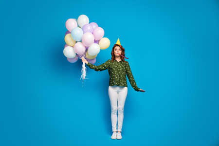 Full size photo of pretty funny lady hold many colorful air balloons best birthday party blow noisemaker wear birthday cap dotted shirt white pants shoes isolated blue color background
