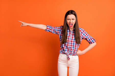 Photo of attractive crazy lady direct finger side showing cheat boyfriend way to go yelling angry wear casual plaid shirt white pants isolated bright orange color background