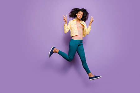 Turned full length body size photo of cheerful toothy beaming girl in pants trousers yellow shirt running junping showing v-sign isolated pastel violet color background