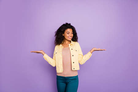 Portrait of confident cool afro american girl promoter hold hand select suggest ads choose decide advise promotion wear modern trousers outfit isolated over purple color background