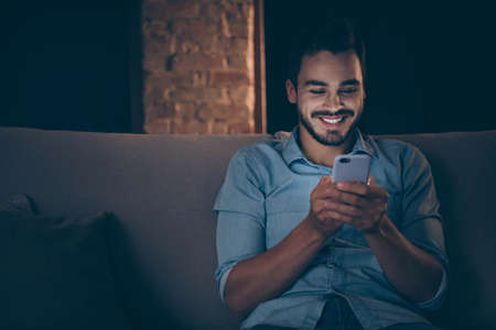 Close-up portrait of his he nice attractive focused cheerful cheery brunet guy sitting on divan using digital device at modern loft industrial style interior dark living-room office