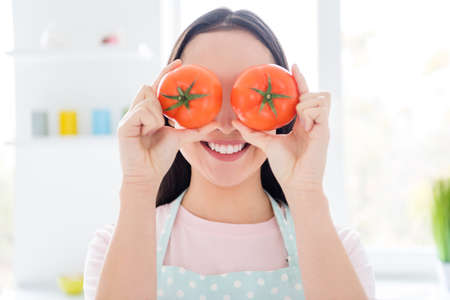 Close-up portrait of her she nice attractive girlish foolish comic cheerful cheery funky girl closing eyes with tomato having fun cooking veg in modern light white interior kitchen