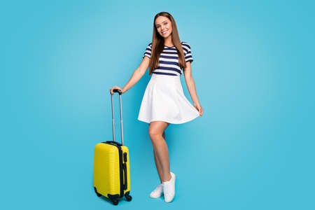 Full length photo of beautiful pretty lady traveler good mood rolling suitcase hands summer vacation resort trip wear striped t-shirt white short skirt shoes isolated blue color background