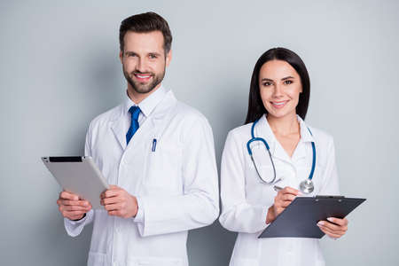 Photo of handsome busy family doc guy lady virology clinic listen client experienced doctors write paper online prescription tablet clipboard wear lab coats isolated grey color background Zdjęcie Seryjne