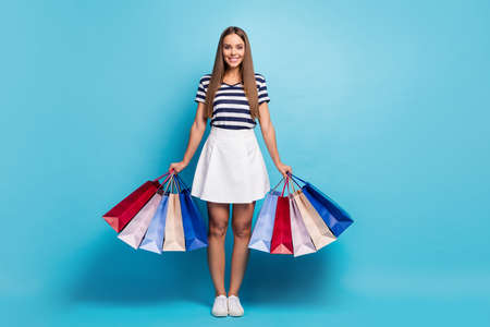Full length photo of charming lady traveler visit shopping center fashion store carry many packs good mood weekend wear white striped t-shirt skirt shoes isolated blue background 写真素材