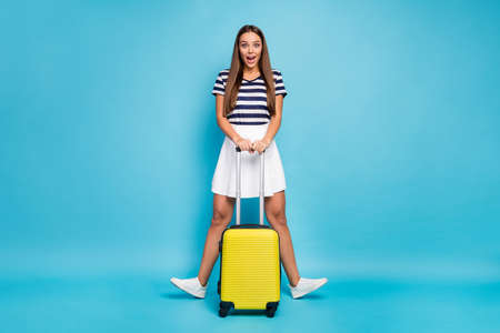 Full size photo of beautiful pretty funky lady traveler good mood rolling suitcase hands long-waited summer trip wear striped t-shirt white skirt shoes isolated blue color background