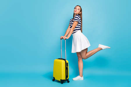 Full body profile photo of beautiful lady traveler flirty sending air kisses rolling suitcase summer journey wear striped t-shirt white short skirt shoes isolated blue color background