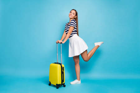 Full body profile photo of beautiful pretty lady traveler flirty mood rolling suitcase summer resort trip wear striped t-shirt white short skirt shoes isolated blue color background