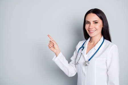 Photo of beautiful doctor direct finger empty space show banner rules safety wear lab coat stethoscope isolated grey color background
