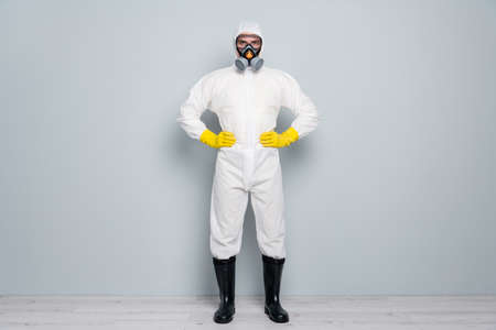 Full length photo of professional guy disinfectant watch public places clean disinfection wear white hazmat protective suit goggles mask gloves gumboots isolated grey color background