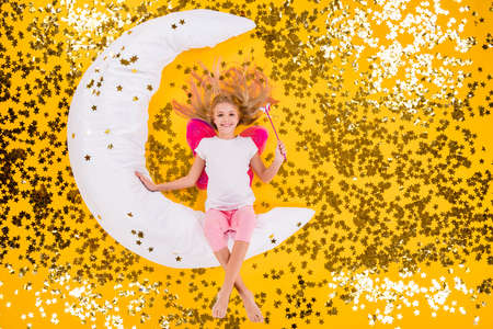Top view above high angle flat lay flatlay lie concept view of little small girl siting on moon using magic stick charm glossy glitter stars isolated bright vivid shine vibrant yellow color background