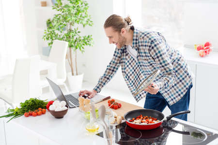 Portrait of his he nice attractive cheerful focused guy making fresh delicious dinner lunch snack salad checking recipe on web site in modern light white interior style kitchen indoors