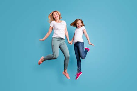 Full length photo of funny mom lady little daughter spend time together jumping high up hold hands good mood wear casual white s-shirts isolated blue color background