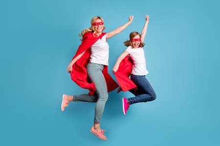 Full body photo of funny mom lady little daughter spend time together carnival super hero costumes jump high up raise fists wear s-shirts red coat masks isolated blue color background 写真素材