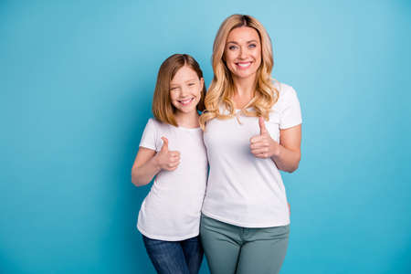 Photo of two people attractive mommy lady little daughter hold thumb fingers raised up express agreement cheerful person wear casual white s-shirts isolated blue color background