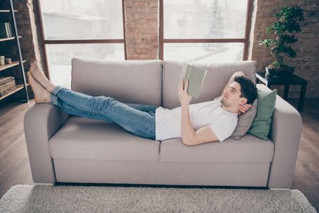 Profile side view portrait of his he nice attractive focused peaceful cheery guy lying on divan reading paper book resting at modern industrial loft brick interior style living-room studio