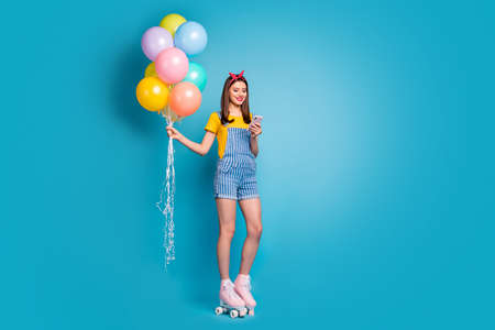 Full length body size view of her she nice attractive lovely cheerful girl standing on roll skates using 5g holding in hands air balls isolated over bright vivid shine vibrant blue color background