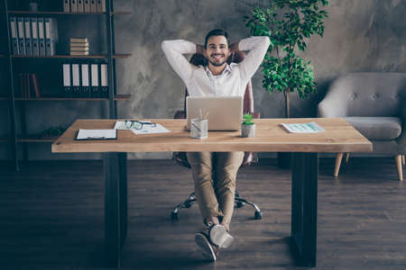 Portrait of his he nice attractive chic confident cheerful cheery glad man skilled HR IT expert shark sitting in chair having rest at modern loft industrial style interior workplace station indoors Stock Photo