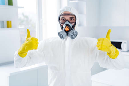 Portrait of successful worker cleaner man in glasses gloves show thumb up symbol approve decontamination covid-19 flu infection procedure wear goggles latex gloves in house kitchen indoors Reklamní fotografie