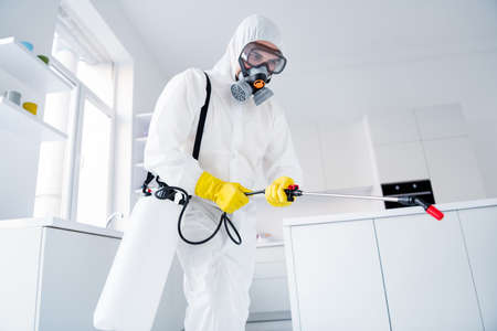 Low angle view photo of focused guy worker hold sprayer latex gloves gas glasses hands spray steam decontaminate ncov epidemic spreading in house kitchen indoors