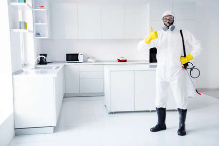 Full size photo of confident successful guy cleaner show in gloves coverall thumb up symbol approve stop spread ncov epidemic treatment wear boots yellow latex gloves goggles in house kitchen indoors