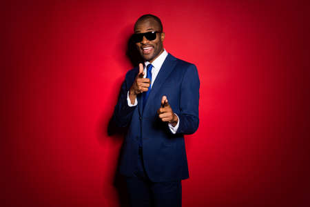 Photo of handsome dark skin business guy cool macho direct fingers say I select you choose new assistant wear sun specs blue formalwear suit tuxedo isolated red burgundy background