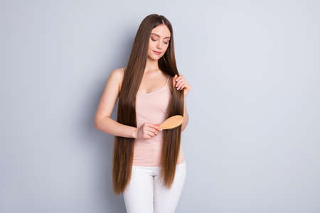 Photo of perfect appearance model lady long hairdo hold favorite wooden comb brushing strong curls wear beige singlet trousers isolated grey color background