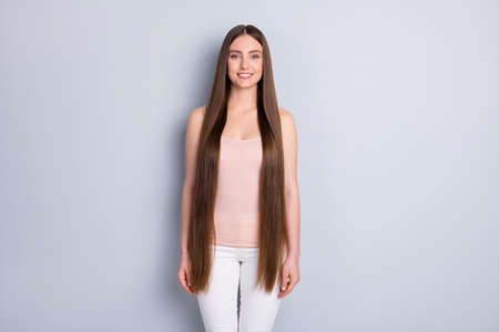 Photo of charming perfect appearance model lady toothy smiling demonstrating ideal neat long hairstyle wear beige singlet white trousers isolated grey color background