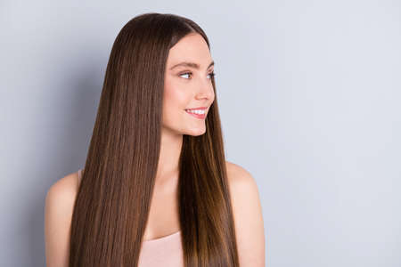 Closeup photo of pretty charming lady white teeth smiling presenting ideal neat long hairstyle look empty space wear beige singlet isolated grey color background Reklamní fotografie