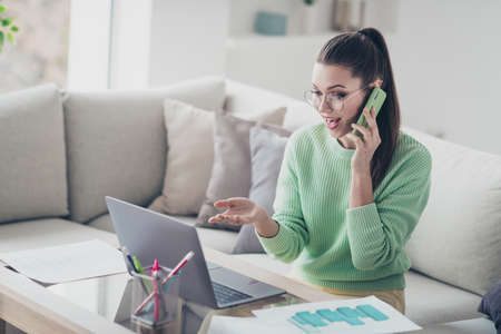 Portrait of her she nice attractive lovely smart clever cheerful cheery glad successful girl calling client partner working remotely discussing project at light white interior room studio flat indoors