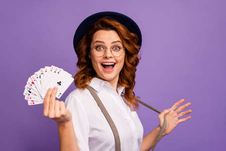 Photo of crazy addicted player lady casino hold poker card deck winner illusionist club risky person wear specs retro cap white shirt suspenders isolated purple color background
