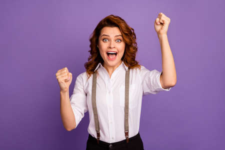 Photo of attractive funny crazy curly lady cheerful casino player open mouth big cash winning raise fists screaming wear white shirt suspenders pants isolated purple color background
